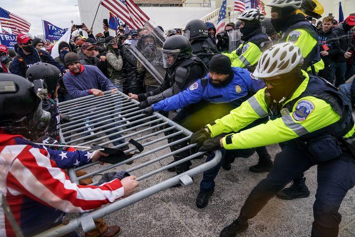 Trump-aanhangers proberen voorbij een politiebarricade te geraken aan het Capitool.