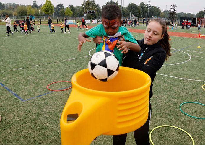 Lodewijk College-leerlinge Alies van Horen helpt Noah een handje om de bal in de korf te krijgen op de Kangoeroedag bij de Terneuzense korfbalvereniging Luctor.