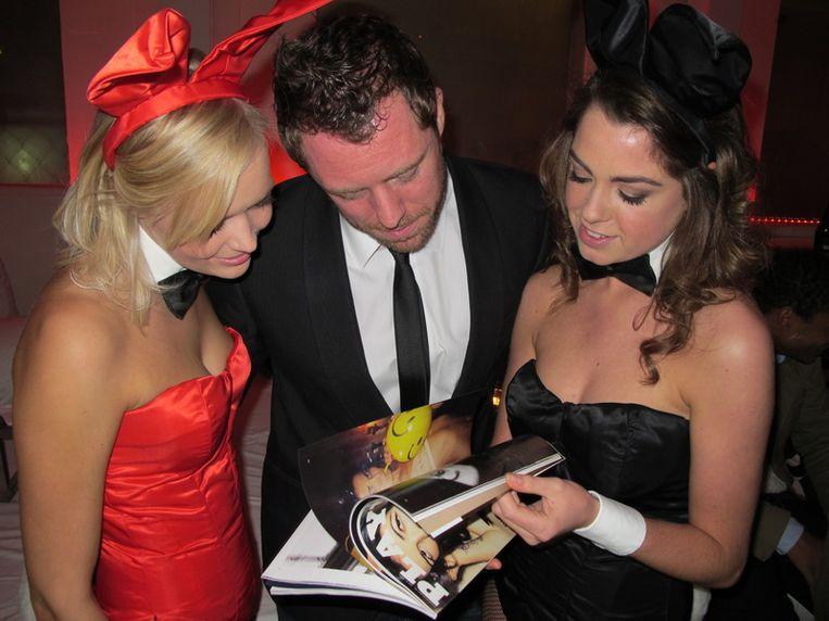 Playboy-product manager Jochem Dielemans leest zich even in met bunny's Malu (l) en Kim. Beeld