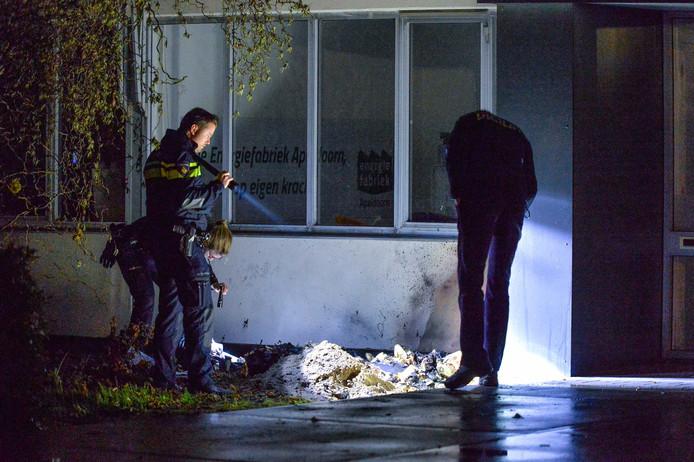 Politieagenten onderzoeken de eerste brand van de nacht.