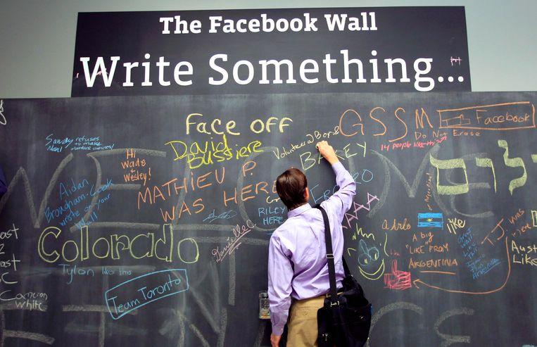 Een werknemer van Facebook laat een mededeling achter op 'The Facebook Wall'. Beeld REUTERS