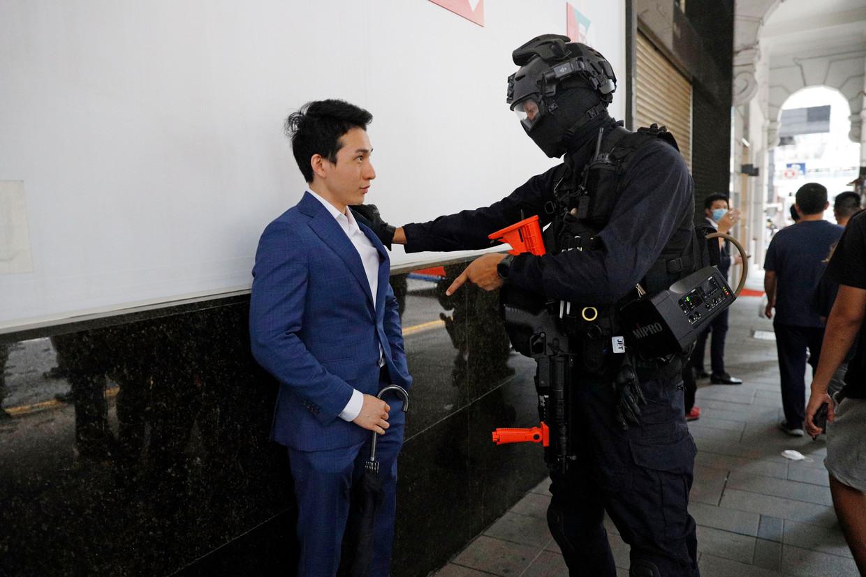 Een agent van de oproerpolitie van Hongkong houdt woensdag tijdens de protesten een voetganger aan. Beeld AP