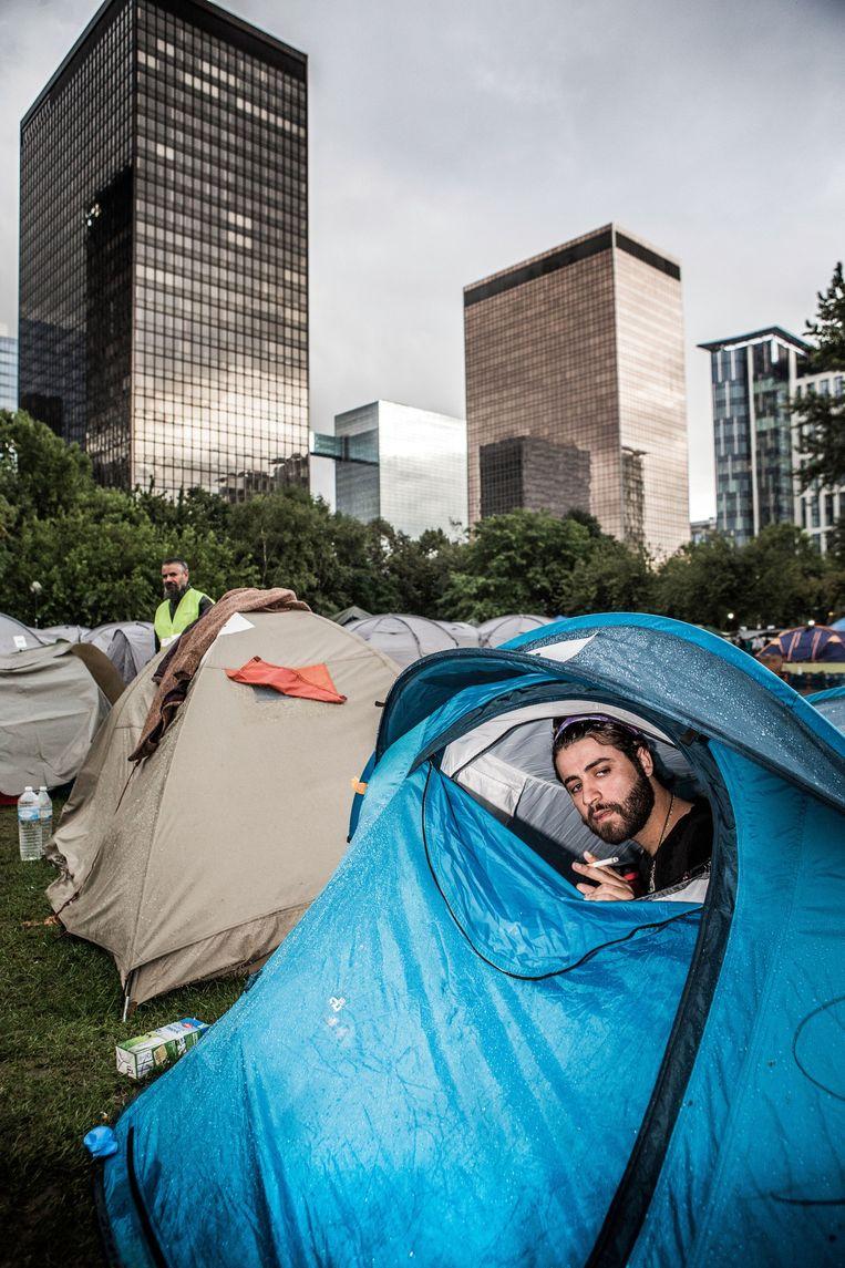 Een vluchteling schuilt in zijn tentje voor de regen. Beeld Bob Van Mol