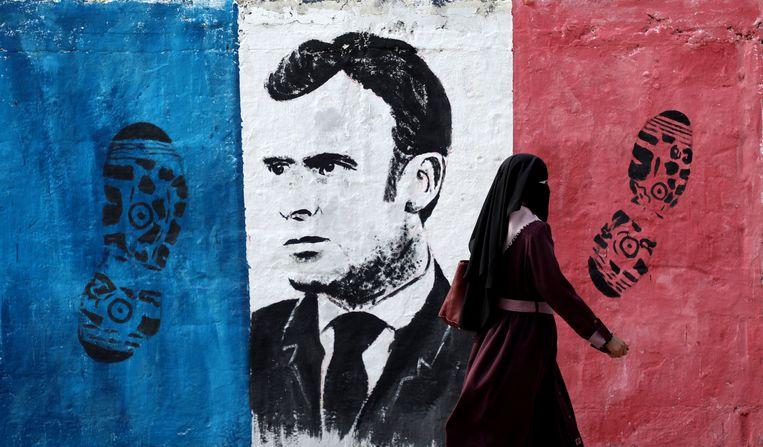 Een Palestijnse vrouw loopt afgelopen woensdag langs een anti-Franse muurschildering met president Macron in Gaza-stad. Beeld Getty
