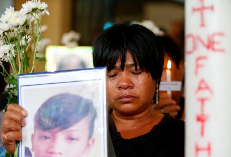 Een vrouw houdt tijdens een katholieke mis in Quezon in het noordoosten van Manila het portret omhoog van een dierbare die het slachtoffer geworden is van Dutertes nietsontziende drugsoorlog.  Beeld AP