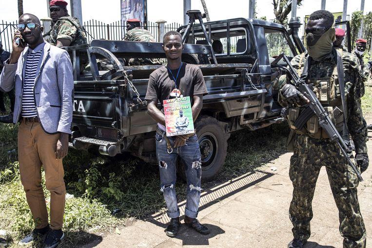 Een aanhanger van juntaleider kolonel Mamady Doumbouya staat met een portret van hem in het Volkspaleis in Conakry. Beeld AFP