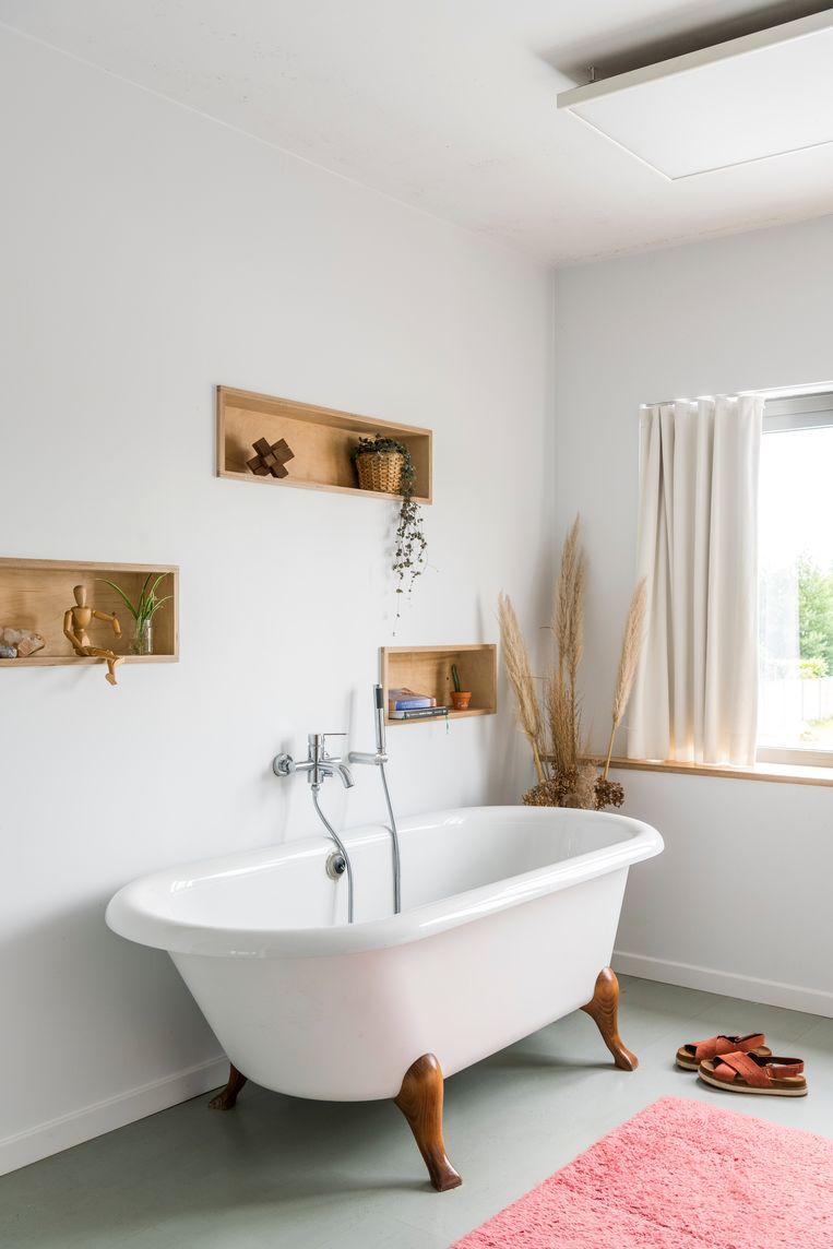 Blikvanger in de badkamer is het designbad op pootjes dat Jeff wist te redden uit een container met bouwafval. De wand met ingebouwde nisjes is een ontwerp van Hanne.  Beeld Luc Roymans