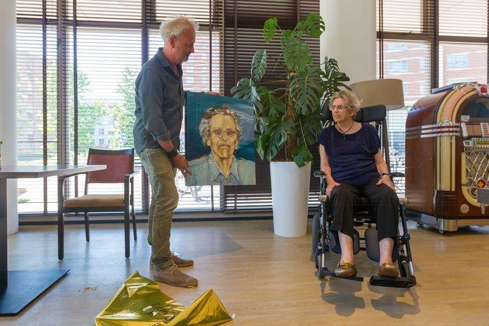 Kunstenaar Antonie de Rooij laat mevrouw Christien Does haar portret zien.