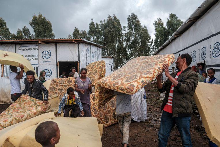 Vluchtelingen in een kamp in Azezo in Amhara krijgen matrassen uitgedeeld. Beeld AFP