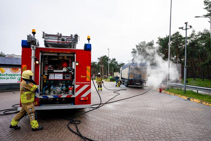 Brandweer blust vrachtwagen die vlam vatte door vastgelopen remmen.