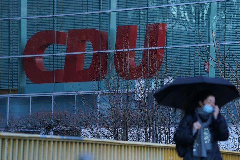 Een vrouw met een mondmasker aan wandelt voorbij het hoofdkwartier van de CDU in Berlijn. Beeld Getty Images