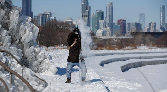 Een man gooit heet water in de lucht, dat onmiddellijk bevriest aan Lake Michigan.