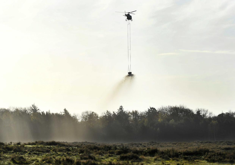 Een helikopter strooit schelpgruis uit voor het bekalkingsproject van de heide en bossen van De Ginkel.