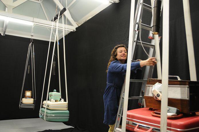 Nanda Runge bezig met de inrichting van haar expositie in in de Bewaerschole. Rechts bovenop een oud vinkenkooitje. Runge maakte er een kijkdoos van