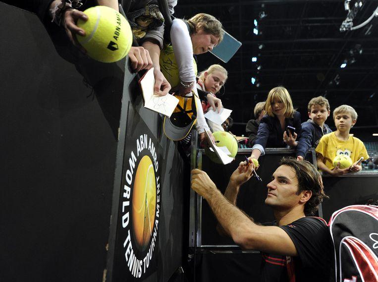 Roger Federer deelt in 2012 handtekeningen uit. Beeld anp