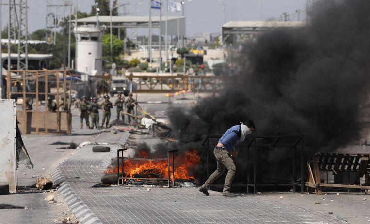 Een Palestijnse manifestant gooit met stenen tijdens een confrontatie met Israëlische troepen op de Westelijke Jordaanoever. Beeld EPA