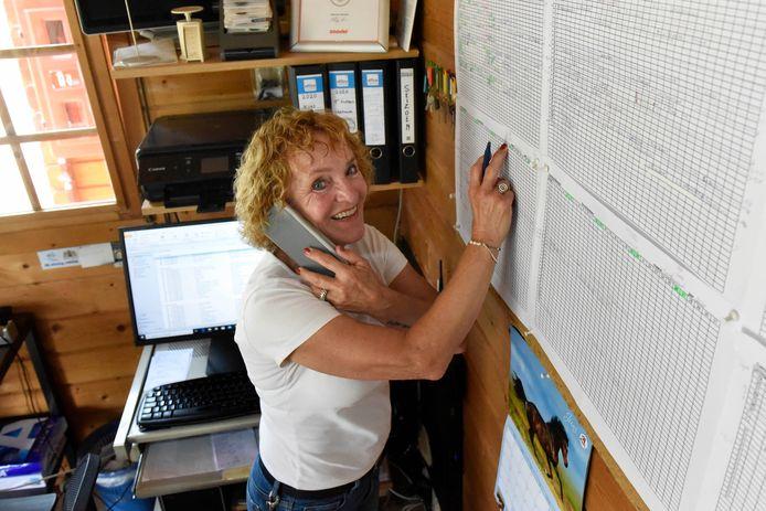 Ineke Hodes van camping Batenstein bezig met de planning achter de balie van de receptie.