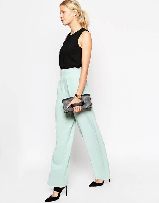 Zo geef je een muntgroene broek een volwassen look: door te combineren met strakke, zwarte accessoires.