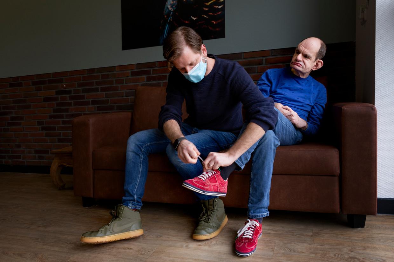 Een deelnemer aan de dagbesteding bij Prinsenstichting krijgt zijn sok met sensoren aan. Beeld Pauline Niks