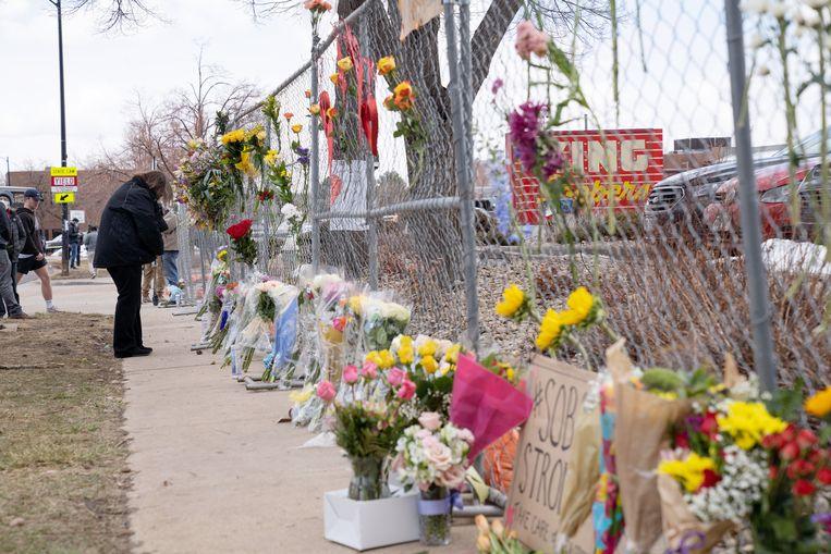 Mensen leggen bloemen neer bij de supermarkt in de Amerikaanse stad Boulder (Colorado) waar tien doden vielen bij een schietpartij. Beeld EPA