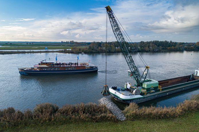 De laatste grijper met x-vormige betonblokken is vanochtend op de flexibele krib gestort, onder toezicht van een boot vol genodigden.