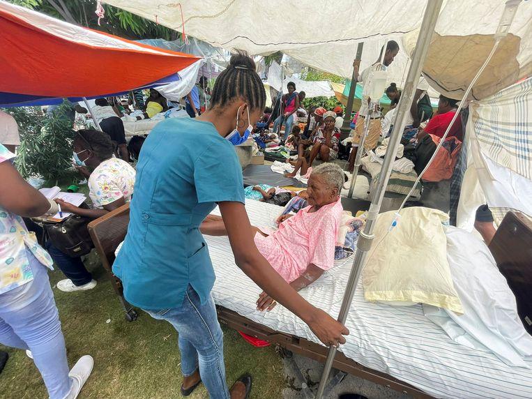 In het zwaar getroffen Les Cayes krijgt een gewonde vrouw medische hulp. Beeld REUTERS