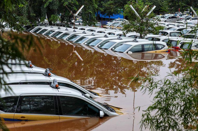 Op een parkeerterrein van een taxibedrijf werd een complete vloot taxi's overspoeld door het water. Beeld AFP
