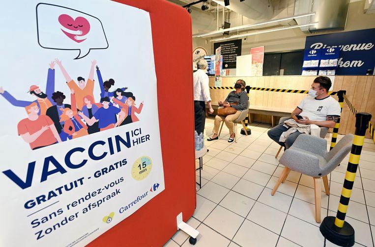Wachten op een vaccin in de Carrefour van Evere. De vaccinatiegraad in Brussel loopt achter en dat zorgt voor nervositeit bij de Franstalige politici. Beeld Photo News
