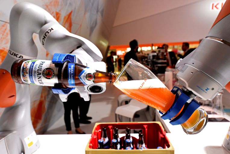 Een robotarm van het Duitse bedrijf Kuka vult een glas met Bavaria Weiss bier op de 'Hannover Fair'. Beeld REUTERS