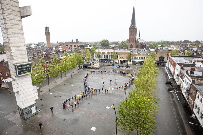 Mensen maken een keten op het marktplein om te symboliseren hoe groot het nieuwe gebouw De Hijschkamer wordt.