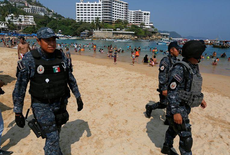 Politieagenten lopen over het strand in Caleta waar veel toeristen hun vakantie vieren. Beeld ap