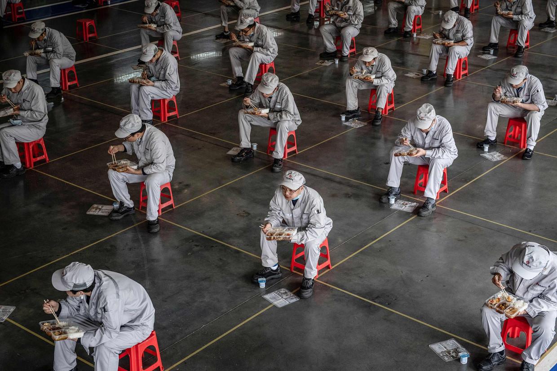Werknemers tijdens de lunchpauze in de Honda-fabriek in Wuhan kort na de uitbraak van corona. Tooze: 'Ik zie de Chinese beleidsmakers zo voor me terwijl ze met grote ogen zitten te kijken  naar hoe het hele Westen er bij de pandemie een janboel van maakt, als een voetbalploeg die de ene owngoal na de andere scoort.' Beeld AFP