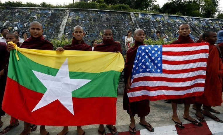 Boeddhistische monniken in Yangon wachten president Obama op, uitgerust met de Birmese en de Amerikaanse vlag. Beeld epa