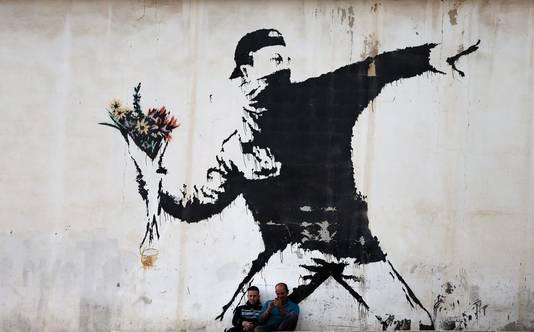 Twee mannen zitten voor een groot werk van Banksy in Bethlehem, op de Westelijke Jordaanoever.
