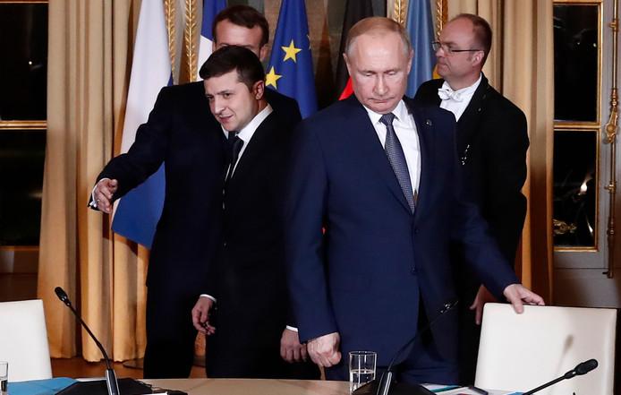 De Russische president Vladimir Poetin (rechts) en Volodymyr Zelenskiy nemen plaats voor een overleg over het conflict in Oost-Oekraïne.