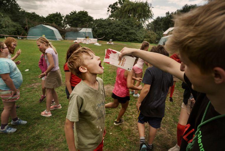 Spelen met fruitdrink: de jongsten van Chiro Bever doen de 'fristikwis'. Beeld Eric de Mildt