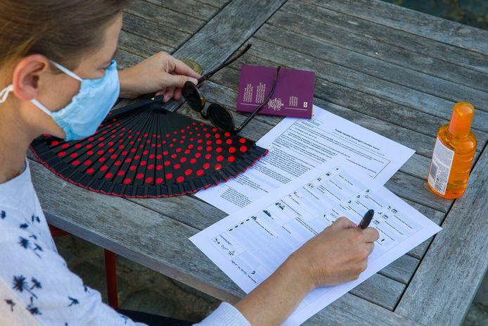 Een vrouw vult het 'terugkeerformulier' in. Elke Belg die minstens 48 uur in het buitenland geweest is, moet de 'Passenger Locator Form' invullen.