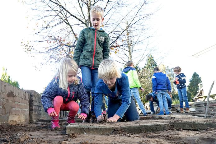Saar, Bram en Hidde (VLNR) zijn met hun klasgenoten hard aan het werk op het schoolplein.