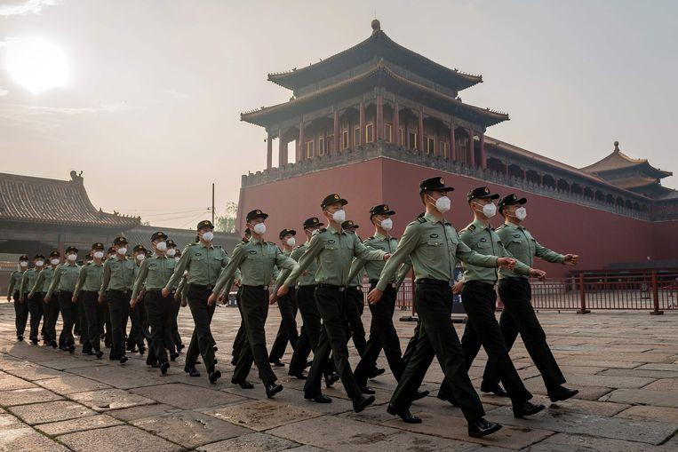Soldaten van het Chinese Volksbevrijdingsleger (PLA) marcheren voor de ingang van de Verborgen Stad in Peking. Beeld AFP