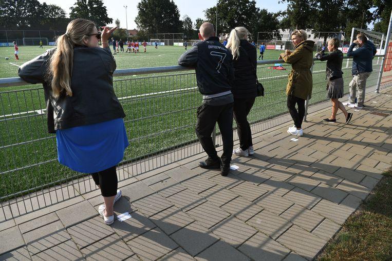 Middels witte stippen langs de lijn worden supporters herinnerd aan het afstand houden. Beeld Marcel van den Bergh / de Volkskrant