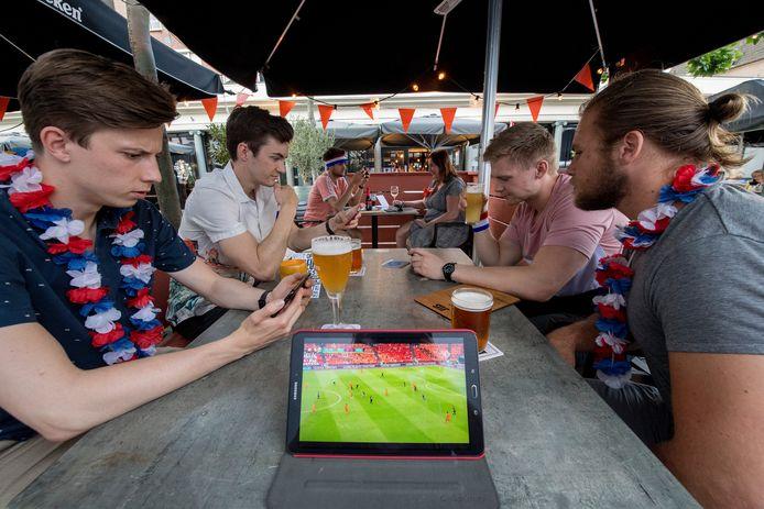 Jan van Mourik (links) kijkt het voetbal op meegebrachte apparaten omdat het gezamelijk kijken op een groot scherm vanwege corona nog niet mogelijk is.