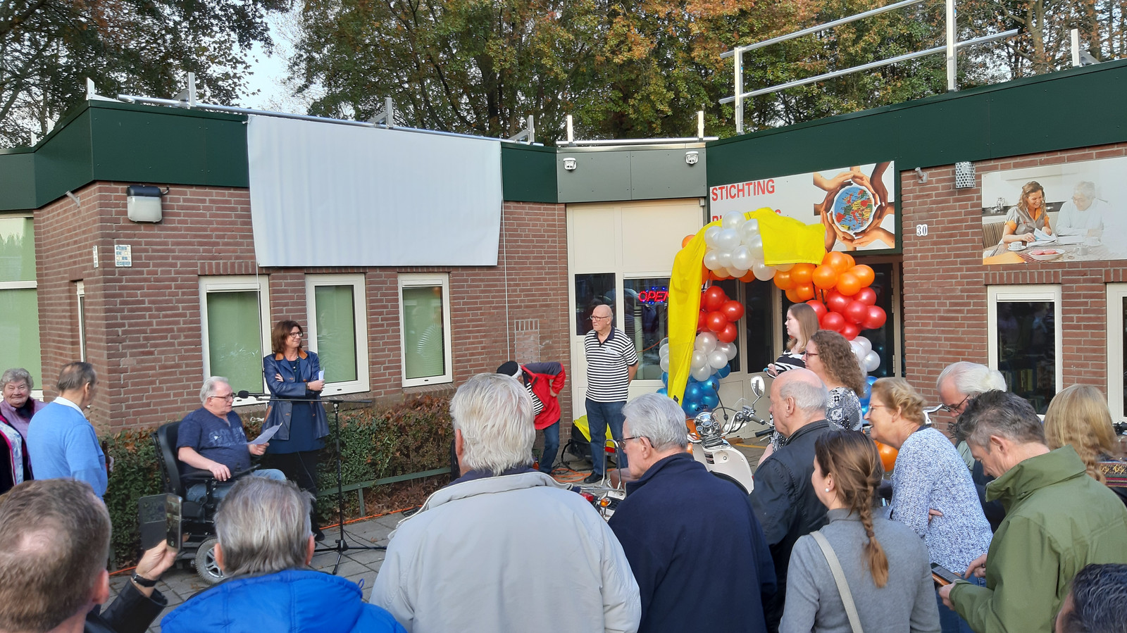 De heropening vrijdagmiddag van buurthuis Geeren-Noord in Breda, dat compleet verduurzaamd is. Met voorzitter Henk Ras achter de microfoon en wethouder Miriam Haagh.