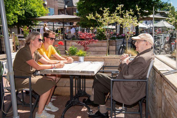 De 99-jarige Marinus de Jonge, zijn kleindochter Bernadet en haar vriend Leon op het terras bij restaurant Puik in Ommen.