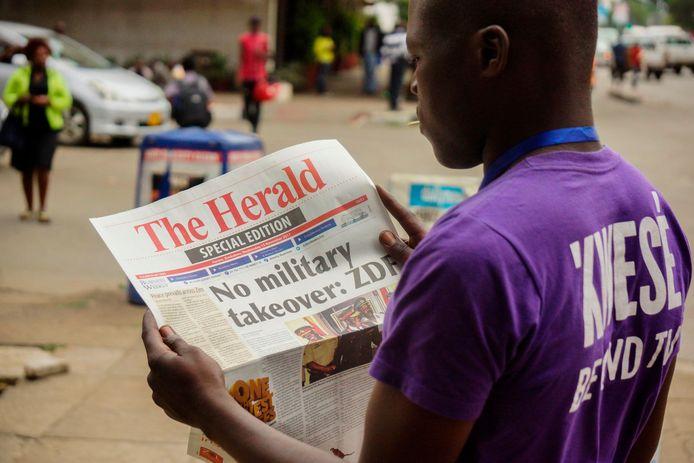 Een inwoner van Zimbabwe leest de laatste berichten over de onrust zijn land.