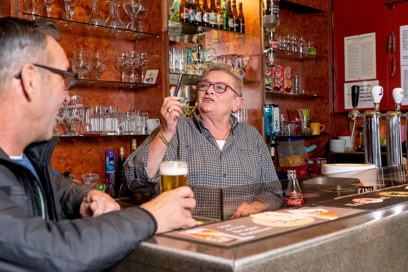 Cafébazin Viviane Debaut (68) achter haar toog, driftig in gesprek met wegenwerker Denis. Hij is een van de vaste klanten voor wie het café een tweede thuis is.