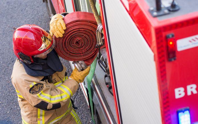 Een brandweerman pakt brandslangen uit de autospuit.