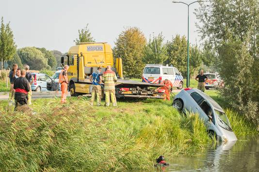 Hulpdiensten takelen de auto waar moeder en kind in zaten op het droge.