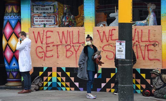Een plek waar daklozen wonen in San Francisco. Een dokter doet een mondkapje op voordat hij met de mensen in gesprek gaat.