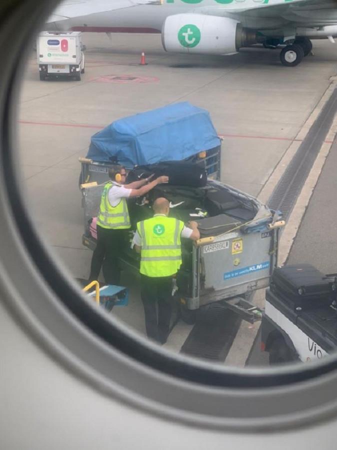 Transavia-piloten helpen bij het inladen van de bagage op Schiphol.