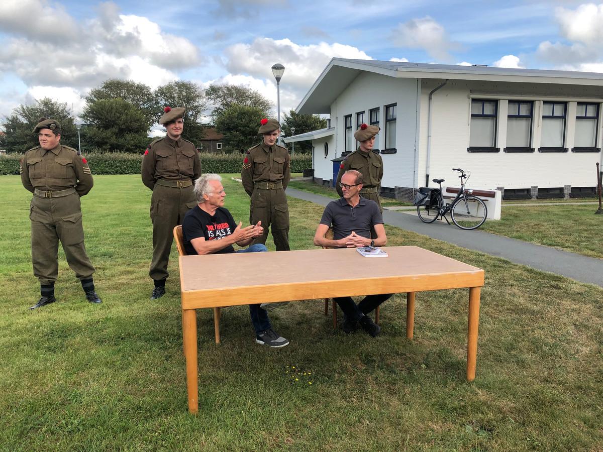 Jelle de Gruyter (links) en Martijn Visser zitten op originele 'capitulatiestoelen' achter de 'capitulatietafel'. Achter het tweetal staan leden van een re-enactmentgroep in Candese legeruniformen uit de Tweede Wereldoorlog.